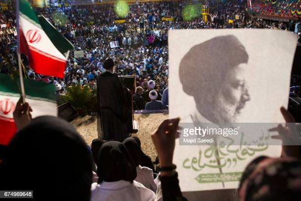 Female supporters of the Iranian cleric presidential candidate Ebrahim Raisi hold his posters as they wave Iranian flags during a campaign rally on...