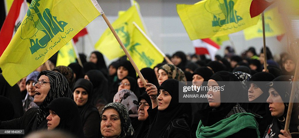 Female supporters of the Shiite Hezbollah movement wave the movement's flag as they watch its chief Hassan Nasrallah, giving a televised speech on the December 4 murder of a top member of the movement, Hassan Hawlo al-Lakiss, in Beirut on December 20, 2013. Nasrallah warned that his Lebanese Shiite movement will 'punish' Israel for the killing of a top leader earlier this month. AFP PHOTO/ ANWAR AMRO