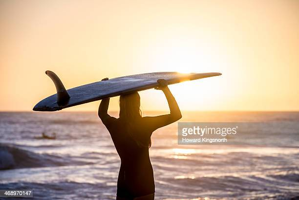 female surfer at sunrise standing on beach