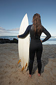 Female surfer standing holding surfboard on beach, back view