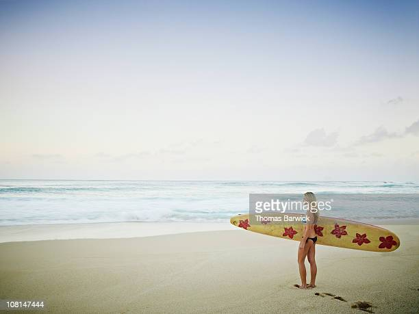 Female surfer standing on beach looking out