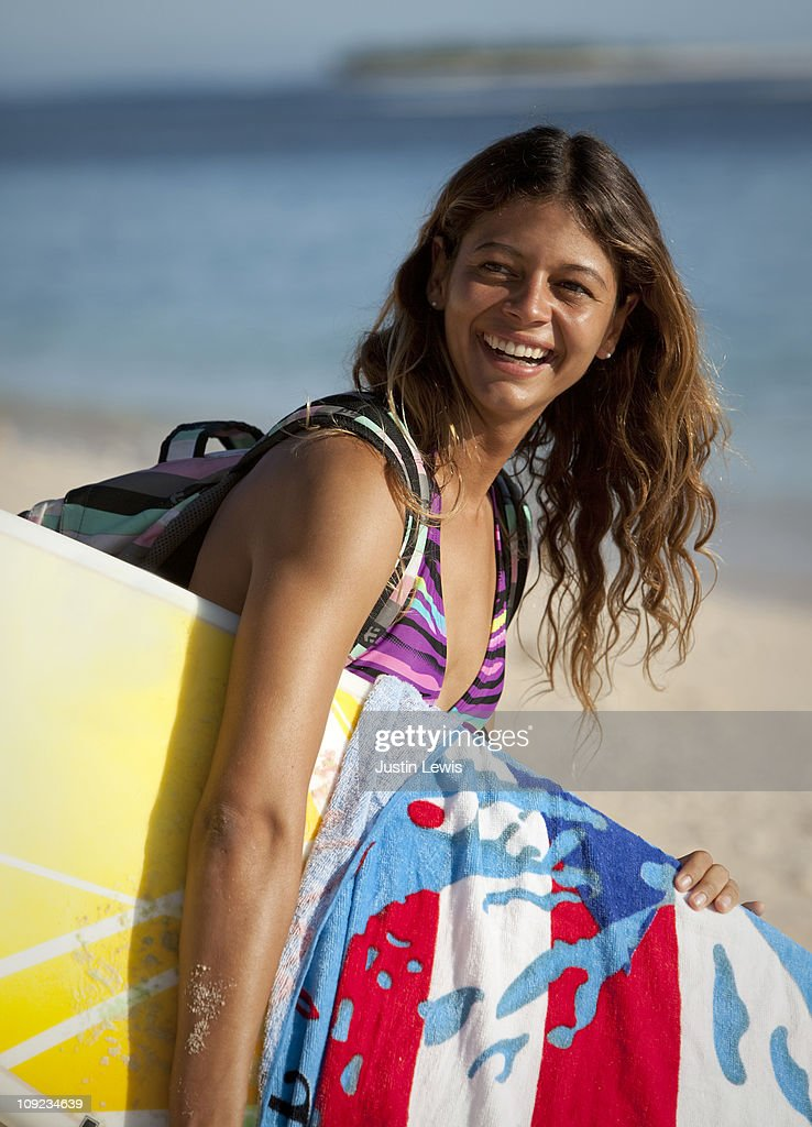 Female surfer walking on beach with her surf board : Stock Photo
