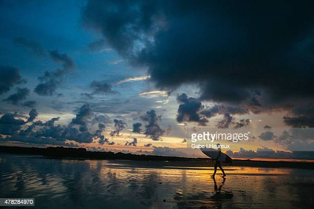 A female surfer walks down beach during sunset on June 13 2015 in Mal Pais Costa Rica