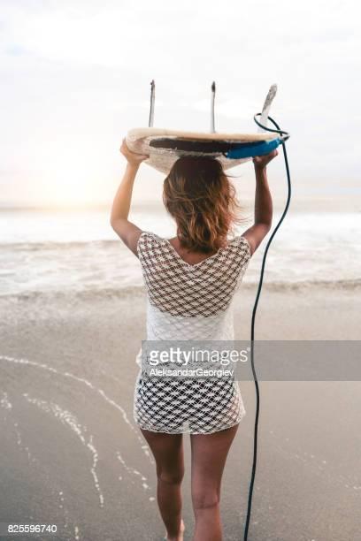 Weibliche Surfer mit Surfbrett geht in Richtung Sonnenuntergang Ozean