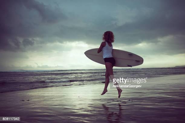Weibliche Surfer mit Surfbrett auf welligen Ozean springen