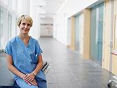 Female surgeon sitting on gurney in hospital corridor, portrait