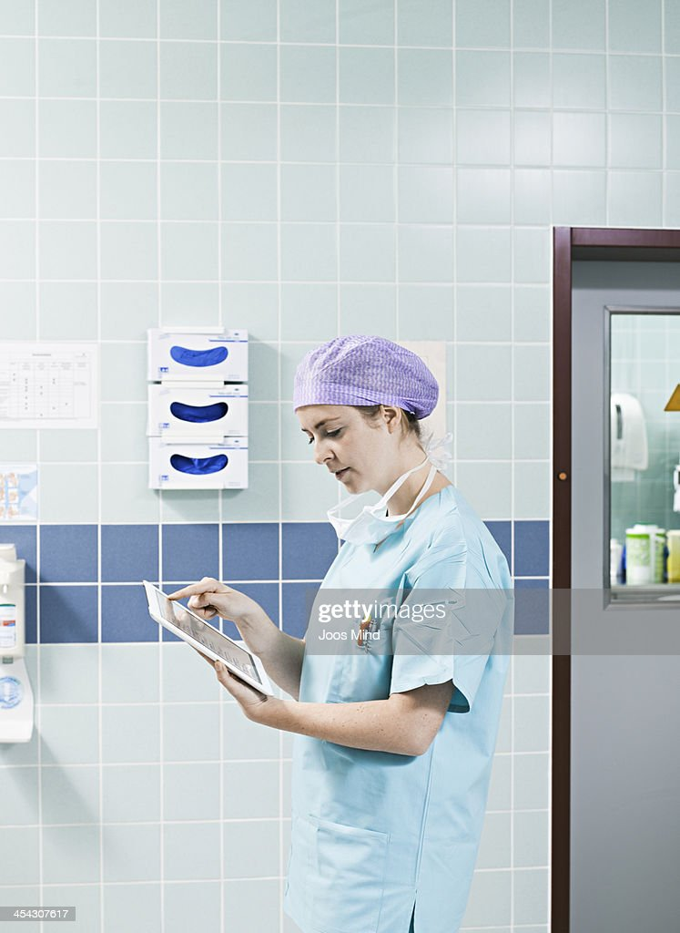 female surgeon using digital tablet : Stock Photo