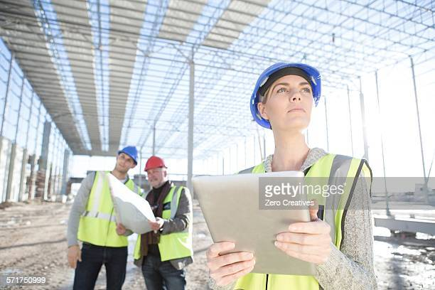 Female surveyor looking up from digital tablet on construction site
