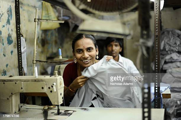 CONTENT] A female sweatshop worker smiles while making shirts for the western market in a small factory in Dharavi Mumbai