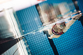 Underwater shot of female athlete swimming in pool. Young woman swimming the front crawl style in a pool.