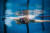 Underwater shot of young sportswoman swimming in pool. Female swimmer in action inside swimming pool.