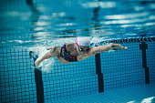 Underwater shot of female swimmer in action inside swimming pool. Young woman training in the pool.