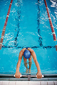Female swimmer in pool, holding onto starting block, elevated view