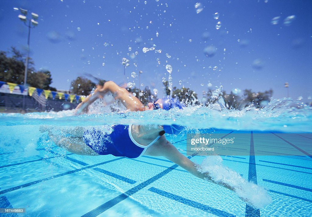 Female swimmer in United States swimsuit swimming in pool : Stock Photo