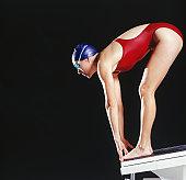 Female swimmer preparing to dive off starting block, studio shot