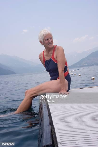 female swimmer sitting on diving platform