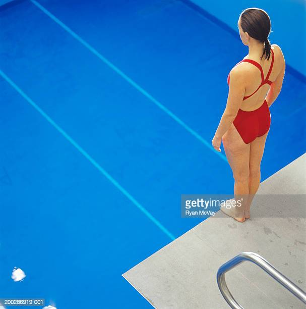 Female swimmer standing on diving board above pool