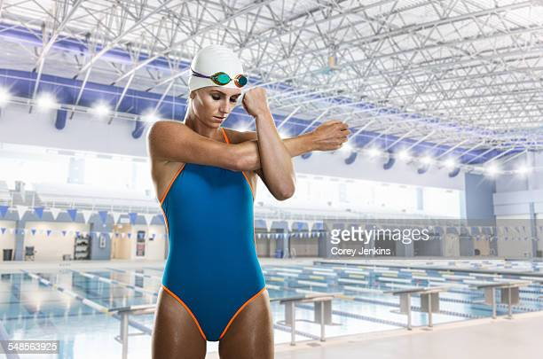 Female swimmer stretching by swimming pool