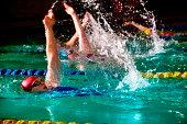Female swimmers doing backstroke in swimming pool