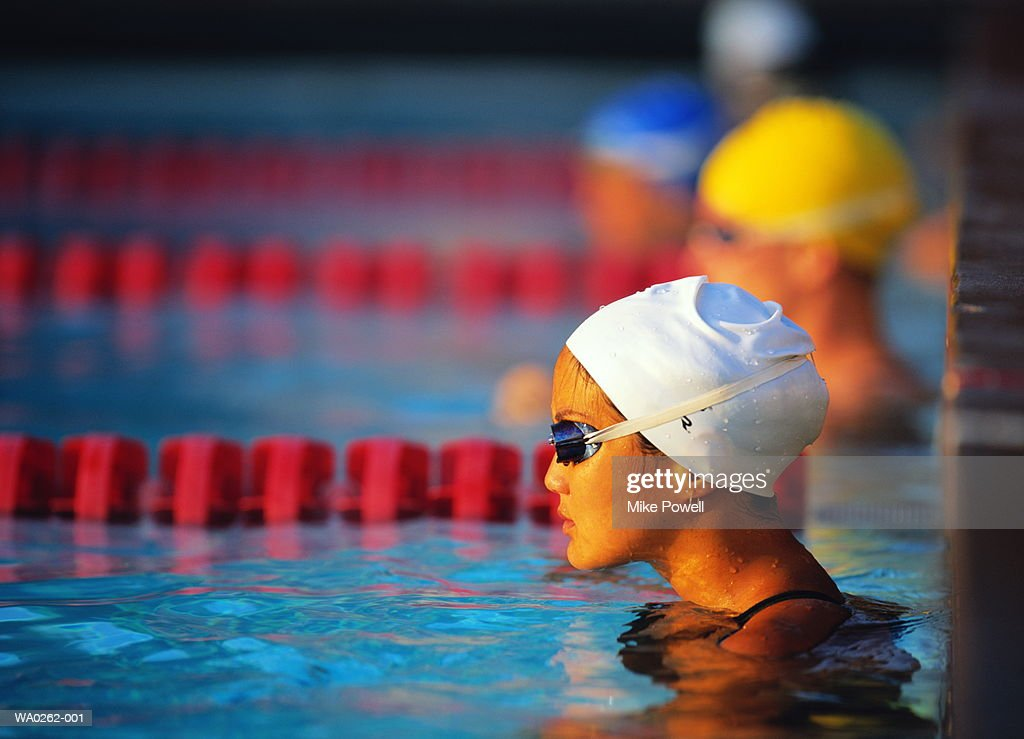 Female swimmers waiting in marked lanes in swimming pool : Stock Photo