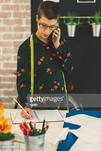 Female Tailor Talking On The Phone In Her Workshop