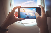 Female taking a photo with smartphone on plane.Holiday travel and journey concept ideas