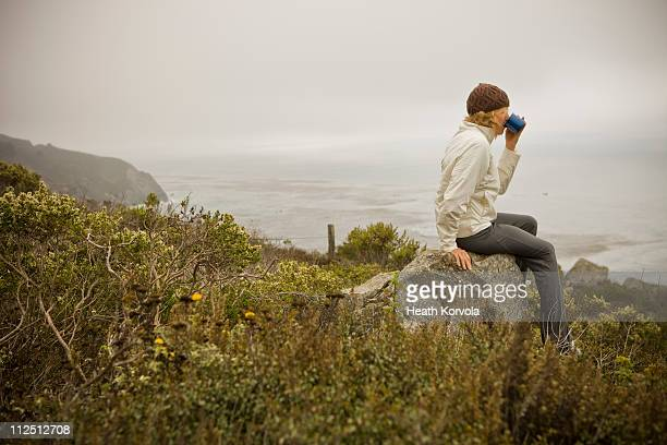 Female taking in ocean with cup of coffee.