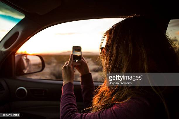 Female taking sunset picture with smartphone.