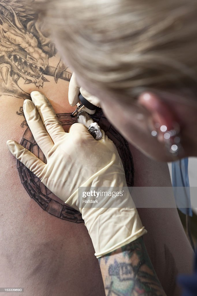 A female tattoo artist tattooing a design on a man's back, over the shoulder view : Stock Photo