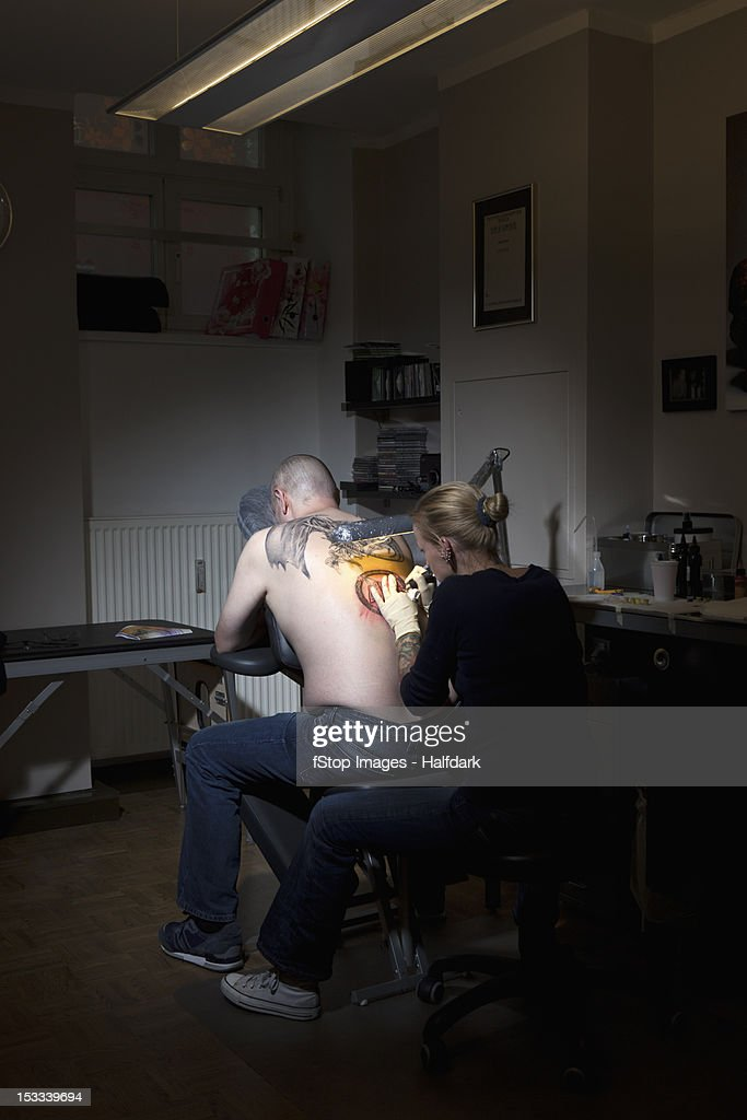 A female tattoo artist tattooing a man's back in a tattoo shop : Stock Photo