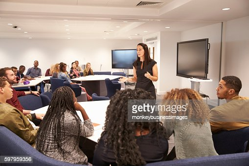 Female teacher addressing university students in a classroom : Stock Photo