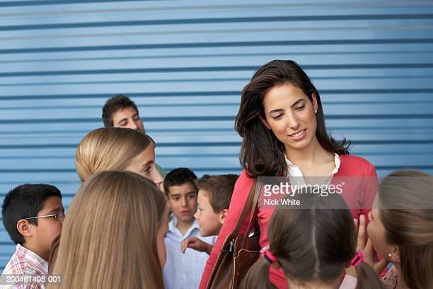 Female teacher amongst group of children (8-12)