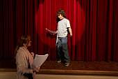 Female teacher and boy (10-12) standing on stage rehearsing