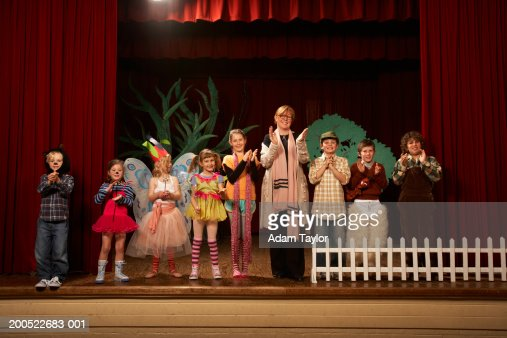 Female teacher and children in play standing on stage, clapping : Stock-Foto