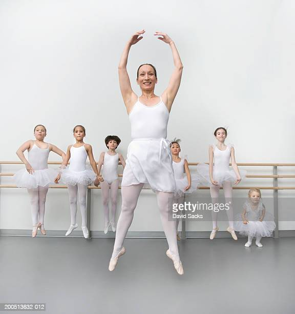 Female teacher and children (3-12) performing jump in ballet class