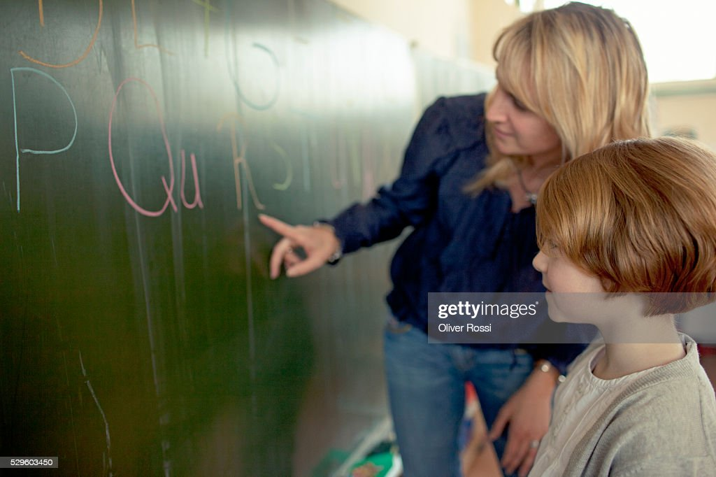 Female teacher and young school boy (6-7) standing by blackboard : Bildbanksbilder