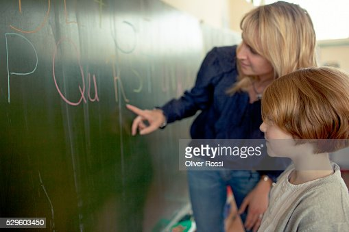 Female teacher and young school boy (6-7) standing by blackboard : Stock-Foto