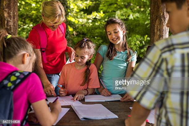 Female teacher assisting children in making their drawings outdoors.