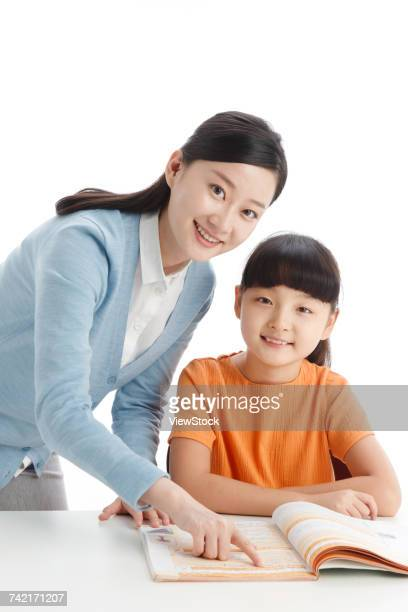Female teacher helping school girl study