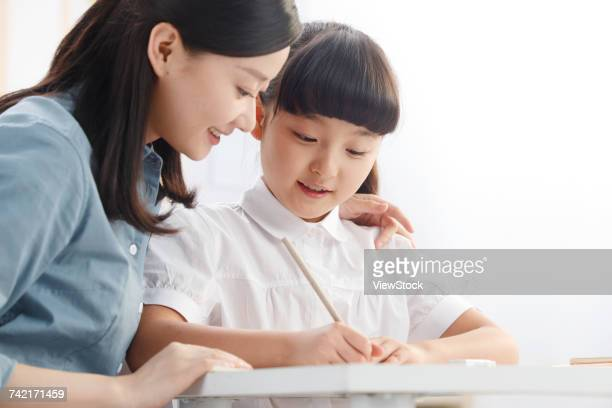 Female teacher helping student studying in classroom