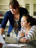 Female teacher helping student working on laptop