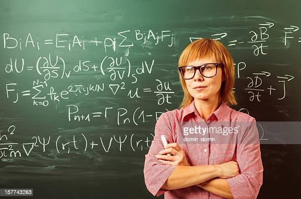 Female teacher in horn rimmed glasses is standing against blackboard