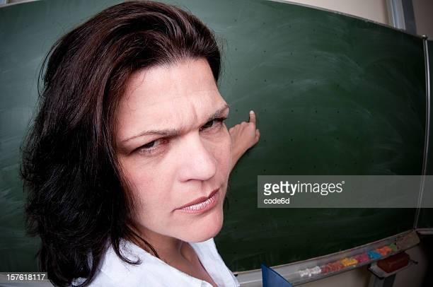 Female teacher standing at blackboard, pointing, fisheye