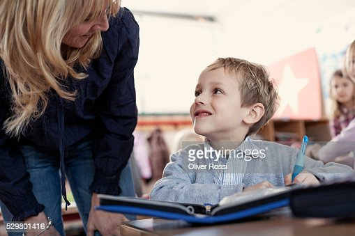 Female teacher talking to pupil (6-7) : Bildbanksbilder