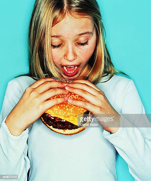 Female Teen Eating a Hamburger