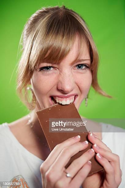 Female teenager biting into a chocolate bar