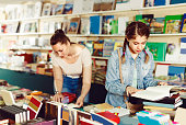 Female teenager is flipping books in bookstore.