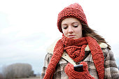 Female teenager wearing a hat and a scarf, holding a mobile phone