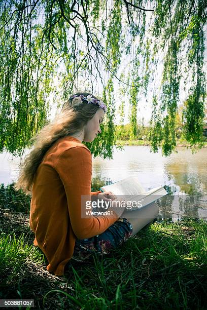 Female teenager with book sitting under weeping willow