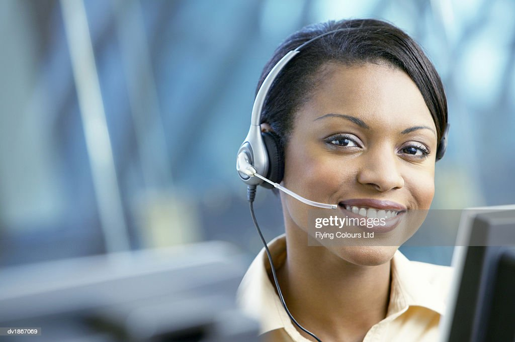 Female Telephonist Sits at a Flat Screen Monitor Wearing a Headset : Stock Photo